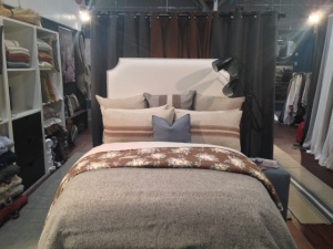The bed is dressed with the Brick Lane floral pattern; the Grain Hall coverlet and shams; and the Heritage Flax organic bedding; and Grain hall striped pillow shams